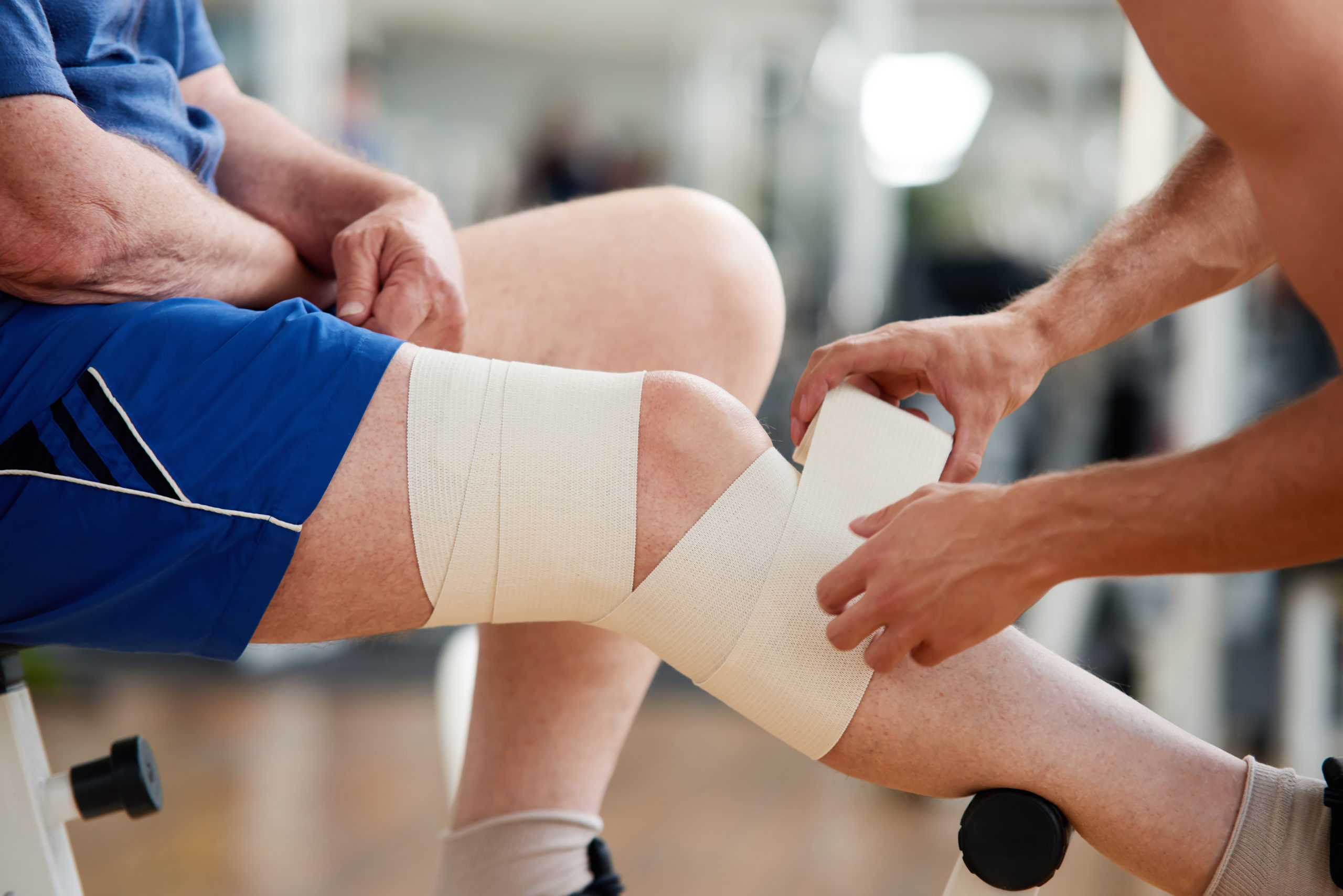 Athletic trainer wraps an athlete's leg with a support bandage after an injury.