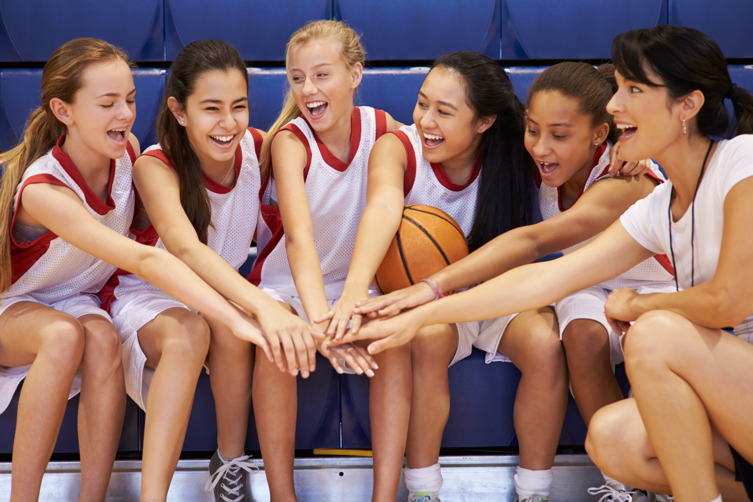 Happy teenage girl basketball players seated in gym reaching hands into a circle with a female coach.
