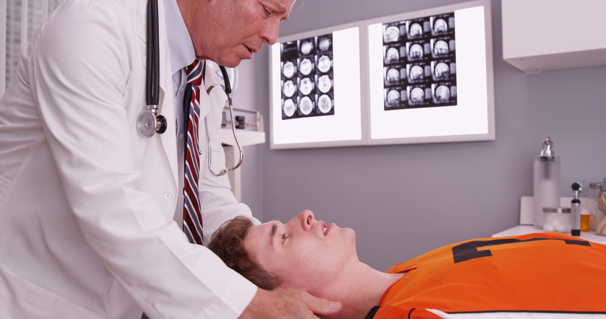 Young male in orange football jersey has his head and neck examined by an older doctor with X-ray images in the background.