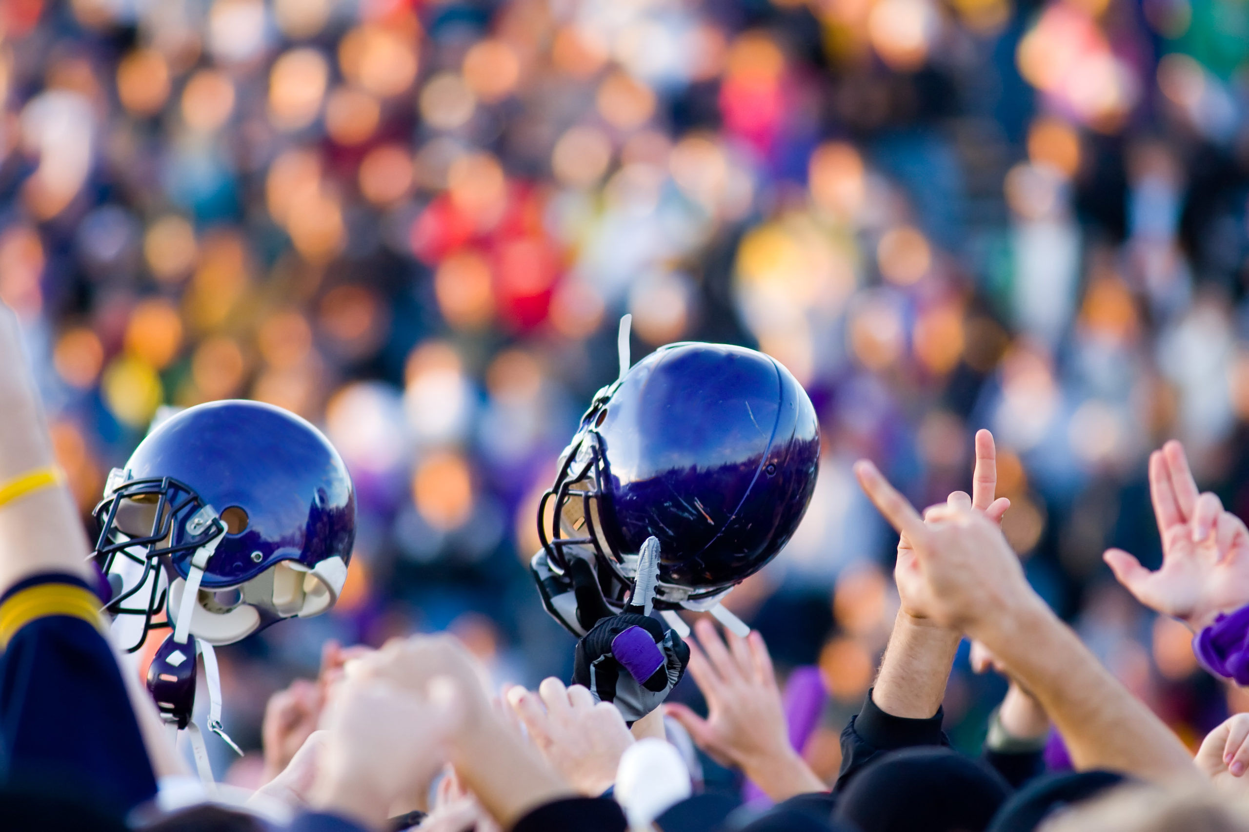 Close up of blue football helmets held in the air in victory against a blurred crowd.
