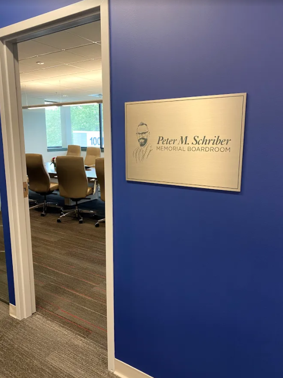 Entrance to boardroom with blue wall and gold memorial plaque.