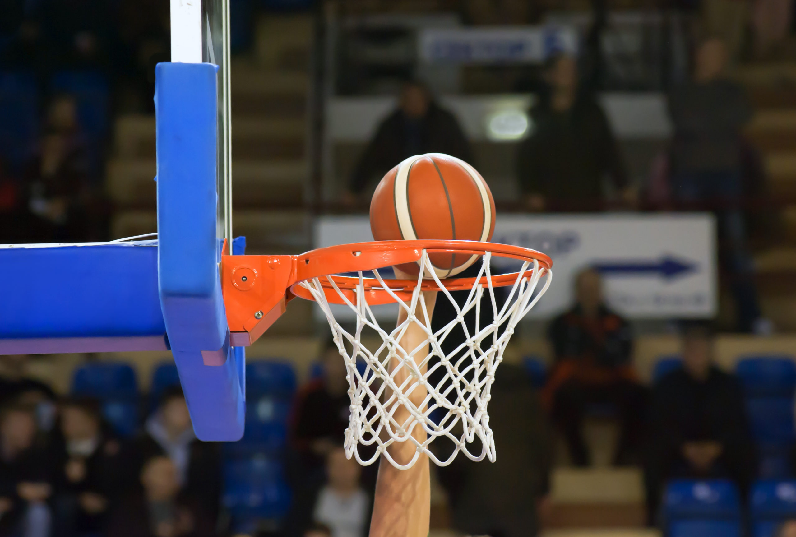 Closeup shot of a basketball player's arm pushing the basketball over the hoop edge into the net.