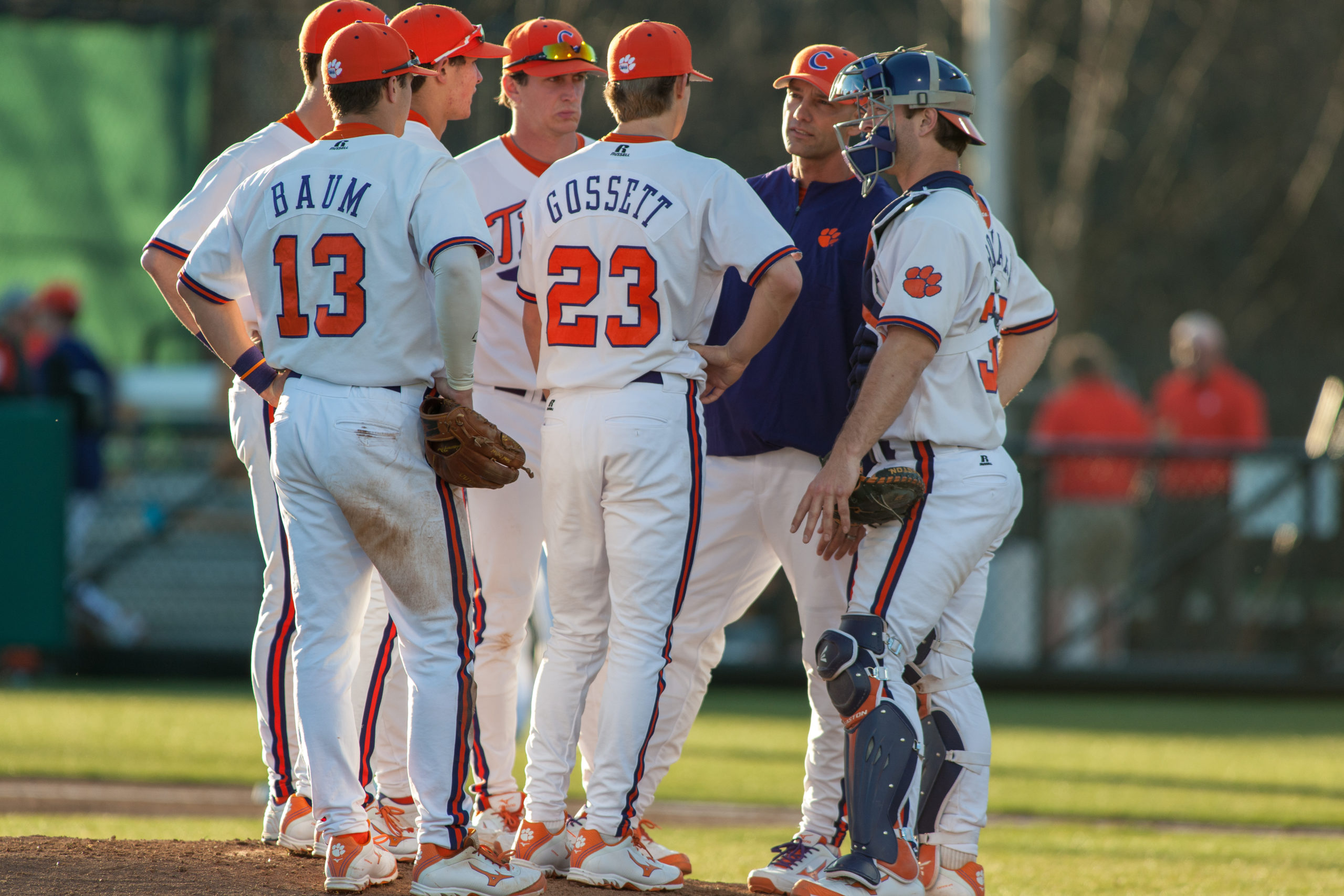College baseball players stand in a huddle at the pitcher's mound.