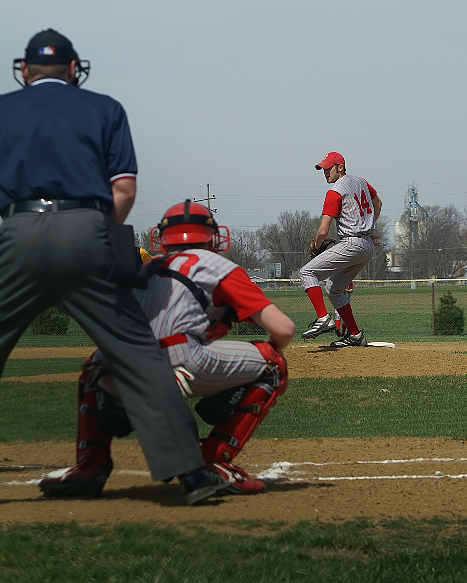 Umpire standing behind catcher at home plate while pitcher winds up his arm at a baseball game.
