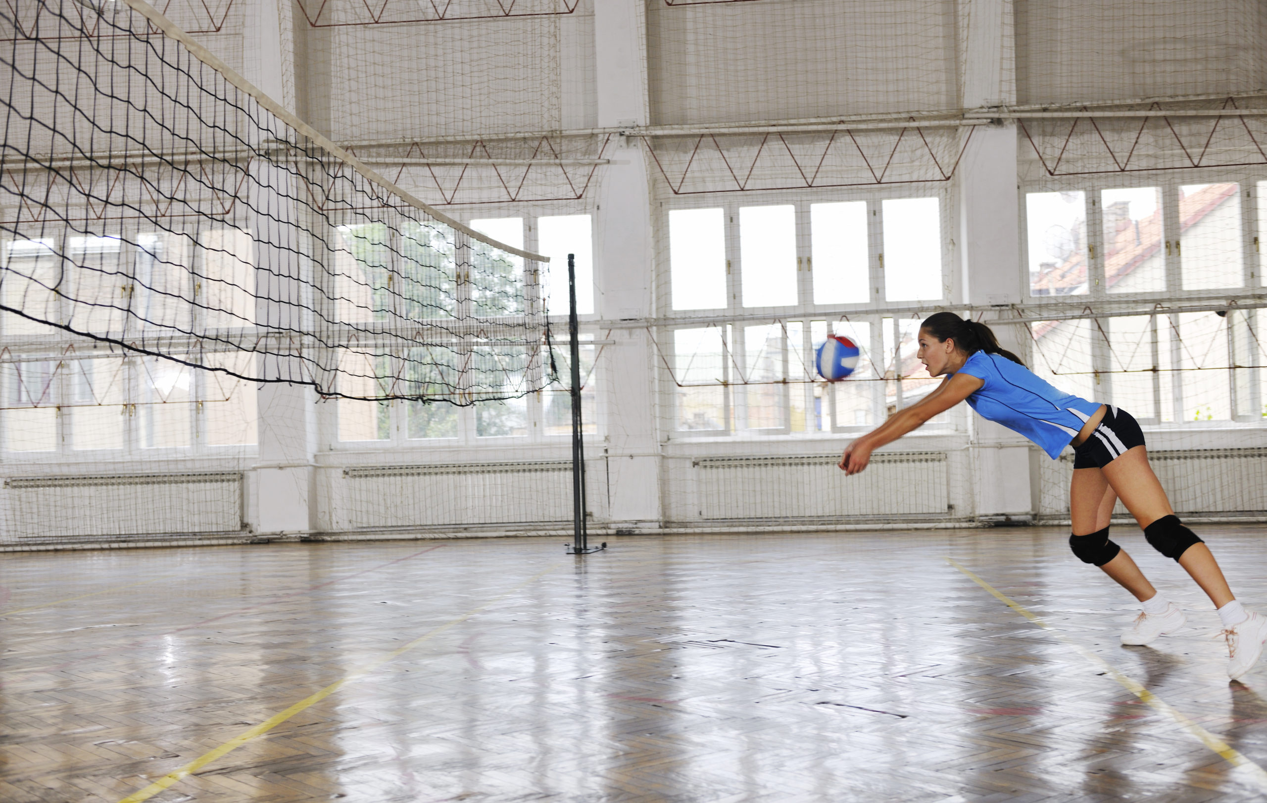 A female volleyball player in a blue jersey leans forward to volley the ball back to the other side