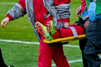 Coach and medic take away injured player from the field on a stretcher.
