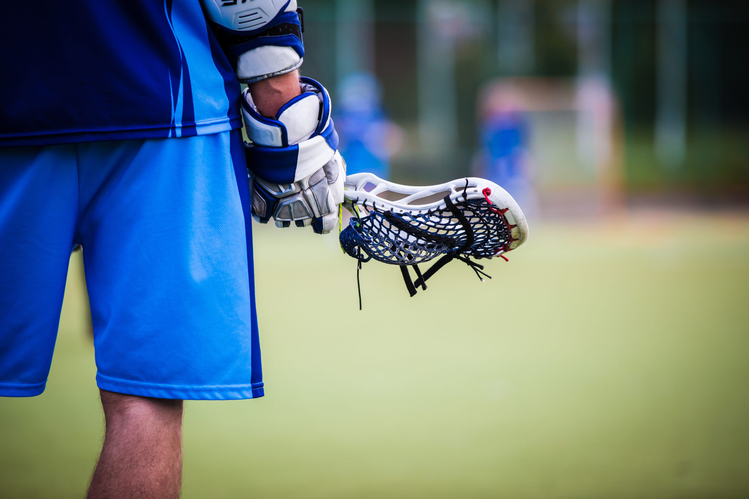 A waist down back shot of a male lacrosse player in blue shorts wearing a glove and holding his lacrosse stick.